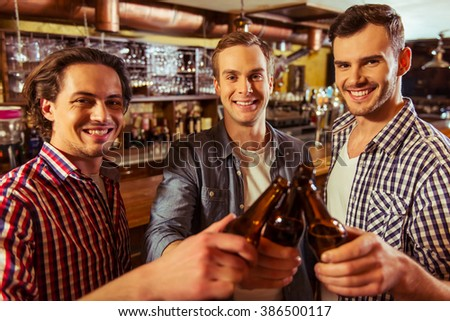 Three young men in casual clothes are smiling, looking at camera and clanging bottles of beer together while standing near bar counter in pub - stock photo