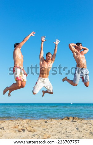 Three young muscular men jumping on the beach - stock photo