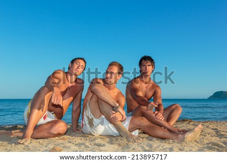 Three young muscular men on the beach - stock photo