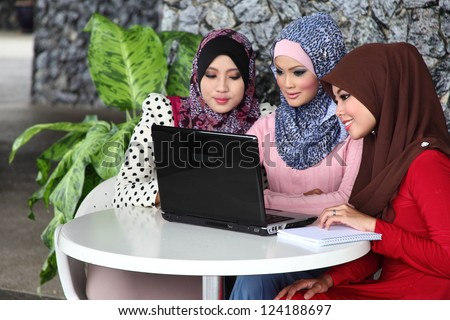 Three young muslim girls with laptop in cafe environment - stock photo