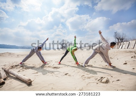 Three young people exercising on the beach - stock photo