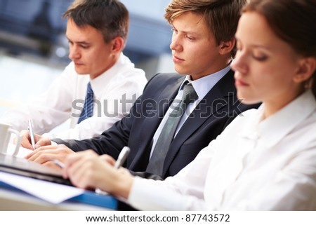 Three young people making notes at lecture with focus on serious student - stock photo