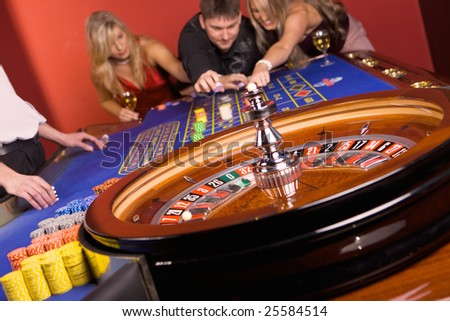 Three young people playing roulette - stock photo