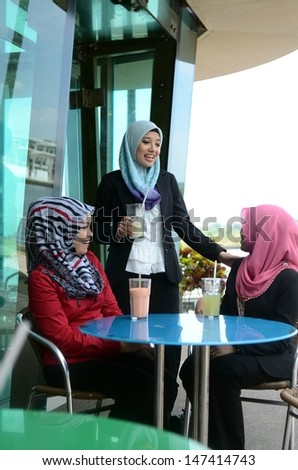 Three young pretty Asian muslim business woman in head scarf drink at cafe - stock photo