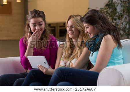 Three young pretty friends watching photos on tablet - stock photo