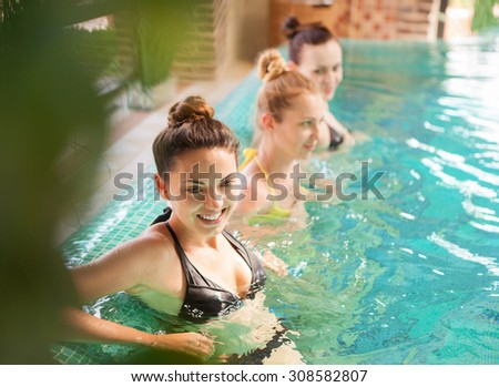 Three young relaxed women in the swimming pool - stock photo