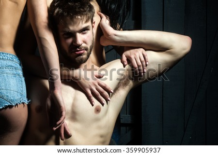 Three young sexy people of handsome bearded muscular macho man holding two sensual attractive girls lovers with beautiful body and naked chest close to each other indoor, horizontal picture - stock photo