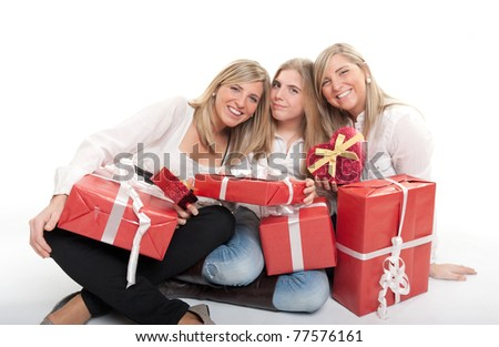 Three young sisters surrounded by gift boxes, some of them heart shaped - stock photo