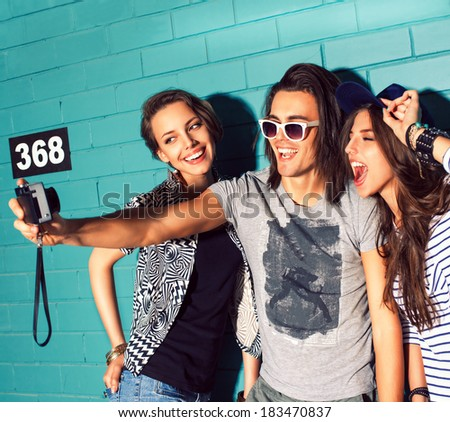 three young smiling people take picture of themselves in front of light blue brick wall - stock photo