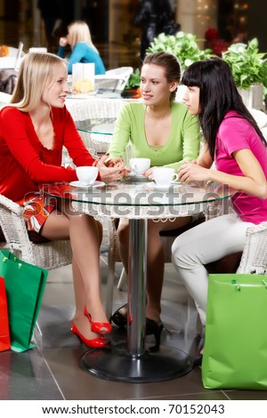 Three young woman drinking coffee in cafe - stock photo