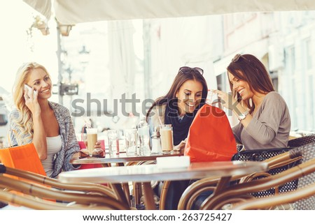Three young women after shopping at coffee - stock photo