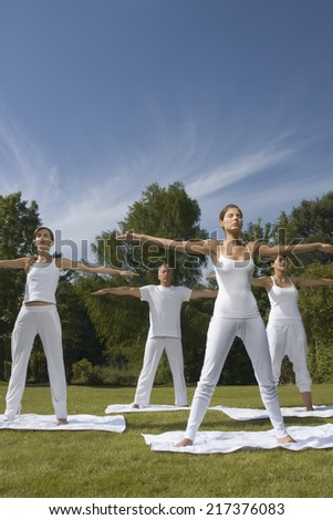 Three young women and a mature man exercising in a park - stock photo
