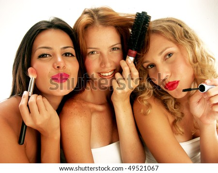 Three young women applying makeup mirror. - stock photo