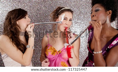 Three young women having a party and blowing whistles on each other, against a silver background. - stock photo
