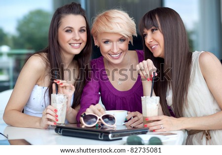 Three young women having coffee break - stock photo