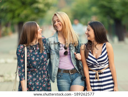 Three young women having fun in the city - stock photo