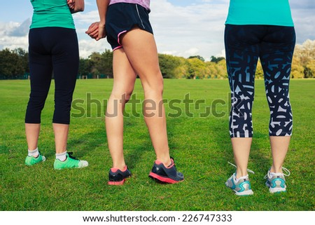Three young women wearing sports clothes are standing on the grass in the park - stock photo