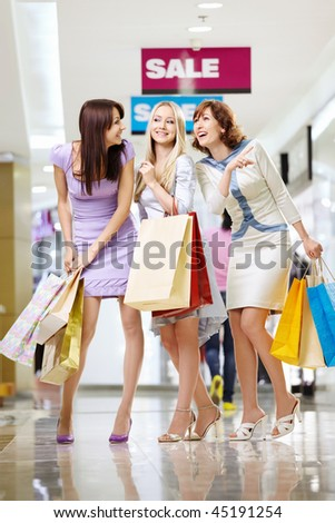 Three young women with bags laugh in shop - stock photo