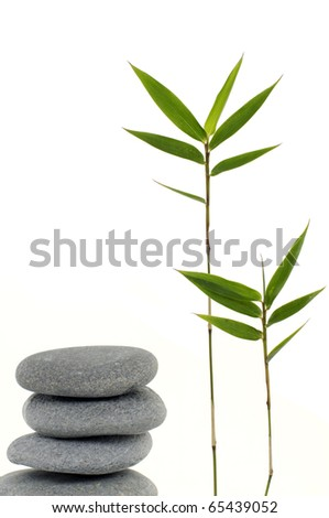 Three zen stones balanced with bamboo leaf - stock photo