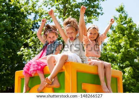 Threesome raising arms together in green park. - stock photo