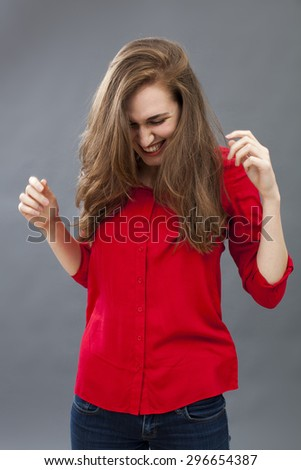 thrilled young woman with long hair wearing red shirt and jeans, looking down for fun expressing joy and wellbeing - stock photo