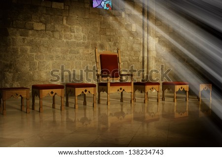 Throne with antique wooden chairs in a dark room with an old stone wall in the background and the rays of sunlight falling from a window, a symbol of power and ruling - stock photo