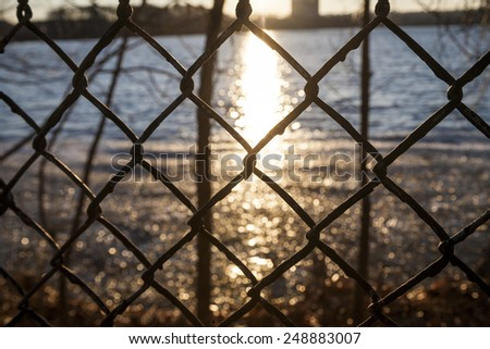 Through the fence sunset on the pond - stock photo