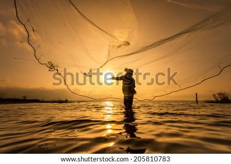 Throwing fishing net during sunset  - stock photo
