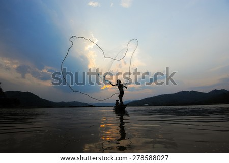 throwing fishing net during sunset on boat , thai, silhouette - stock photo