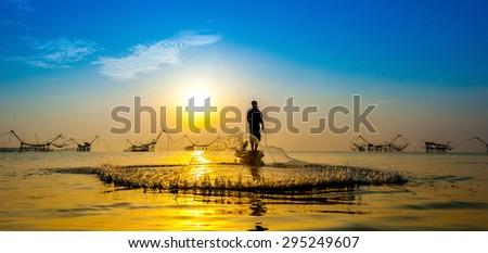throwing fishing net during sunset , thai - stock photo