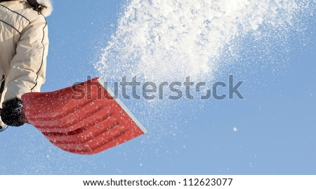 Throwing snow with a snowshovel against blue sky - stock photo
