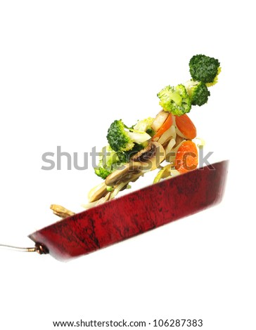 throwing the vegetables. focus on vegetables - stock photo
