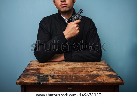 Thug at table with gun - stock photo