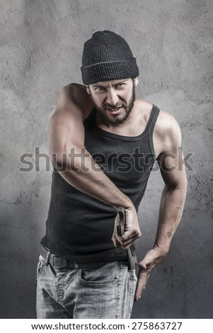 Thug preparing to use a wrench as a weapon pulling it out of the pocket of his jeans as he watches the camera with a dangerous angry expression, over a textured grey background - stock photo
