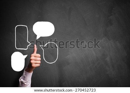 thumb up gesture with speech bubble symbols in front of a blackboard - stock photo
