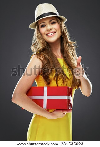 thumb up. joyful woman with long hair hold present. dressed in a yellow dress - stock photo
