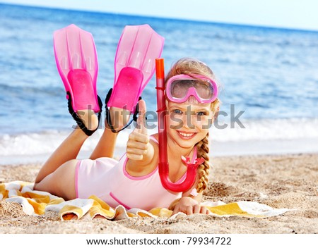 Thumb up of child playing on beach. - stock photo