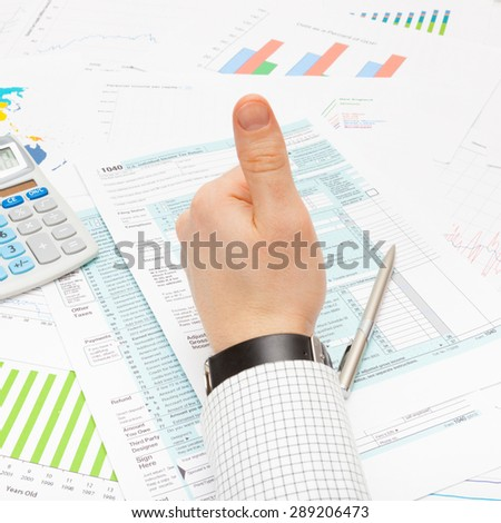 Thumb up over 1040 Tax Form - focus on calculator - stock photo