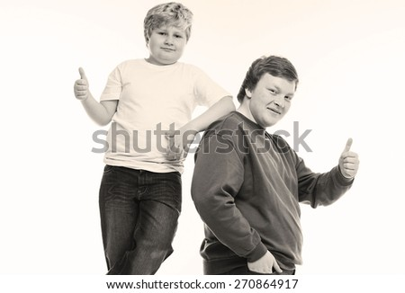 thumb up two boys brothers and friends  studio portrait on white background playing - stock photo