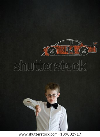 Thumbs down boy dressed up as business man with American racing fan car on blackboard background - stock photo
