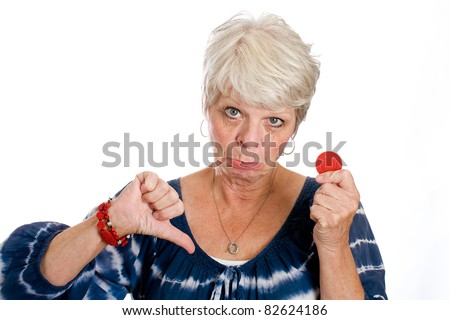 Thumbs down for a mature gray haired woman with her last red poker chip. - stock photo