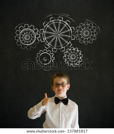 Thumbs up boy dressed up as business man with chalk turning gear cogs or gears on blackboard background - stock photo