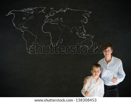 Thumbs up boy dressed up as business man with teacher man and chalk geography world map on blackboard background - stock photo