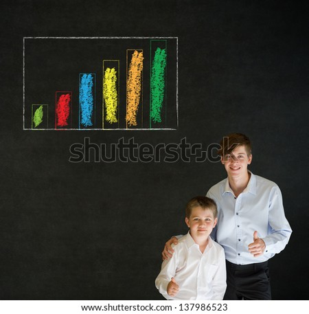 Thumbs up boy dressed up as business man with teacher man and chalk graph or chart on blackboard background - stock photo