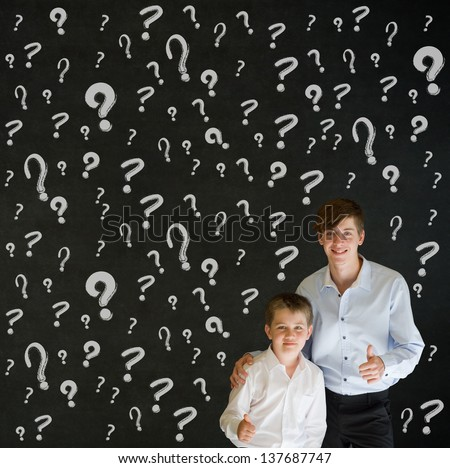 Thumbs up boy dressed up as business man with teacher man and chalk questions marks on blackboard background - stock photo