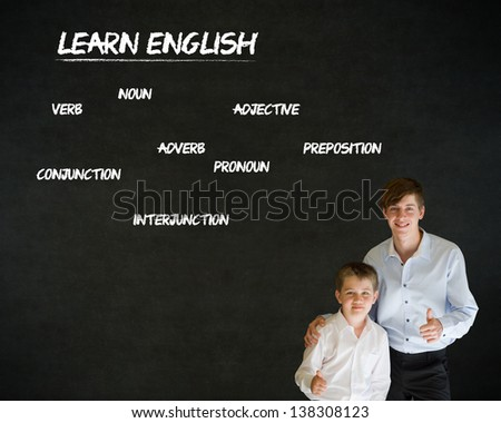 Thumbs up boy dressed up as business man with teacher man and learn English on blackboard background - stock photo
