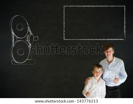 Thumbs up boy dressed up as business man with teacher man and retro chalk film projector on blackboard background - stock photo