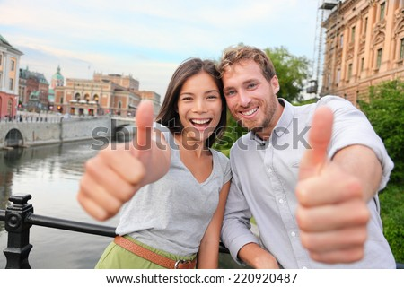 Thumbs up couple happy in Stockholm, Sweden. Excited people giving thumbs up gesture looking at camera. Multiracial young couple walking outside in Stockholm. Scandinavian man, Asian woman. - stock photo