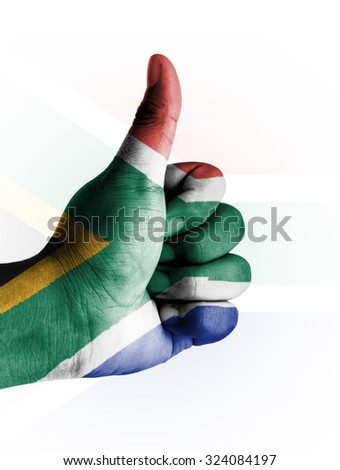 Thumbs up digitally compositing on with South Africa flag - stock photo