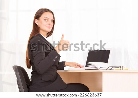 Thumbs up. Modern woman employee of the office. Or a girl student. She sits behind a desk, next to a laptop and diary entries for cases. All is well in business. All right, OK. Raise the thumbs up.  - stock photo